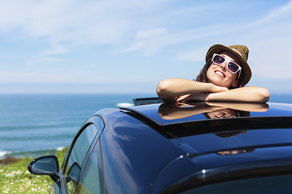woman with her upper body perched out of the sunroof of a car